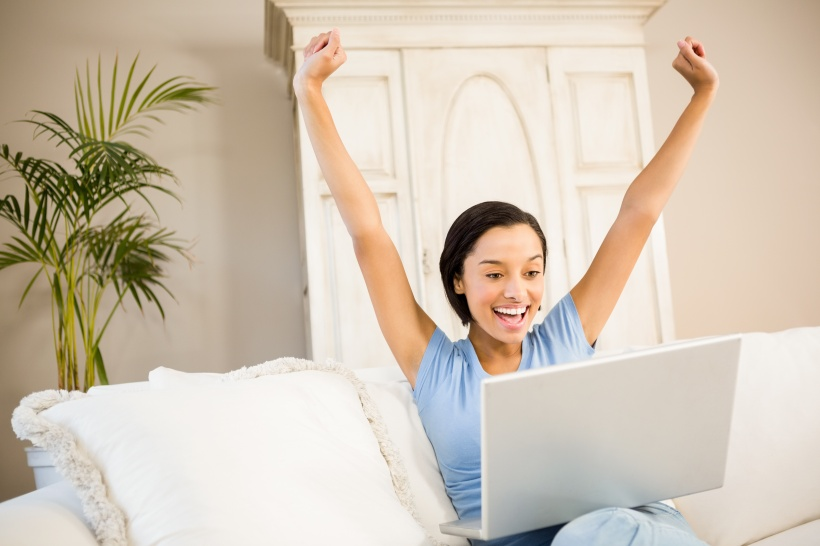 Happy woman using laptop and raising arms